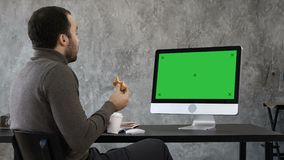Handsome businessman eating and having a video conference with someone. Green Screen Mock-up Display. stock footage