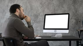 Handsome businessman eating and having a video conference with someone. White Display. stock image