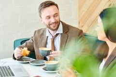 Handsome Businessman Enjoying Breakfast with Colleague stock photography