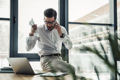 Handsome businessman working. Handsome businessman in eyeglasses is crumpling paper and screaming while talking on the mobile phone in the office Stock Image