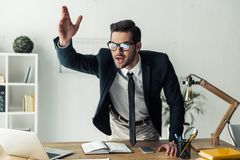 Handsome businessman working. Handsome businessman in eyeglasses is giving orders while standing at his workplace in the office Royalty Free Stock Photos