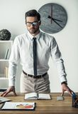 Handsome businessman working. Handsome businessman in eyeglasses is looking at camera while standing at his workplace in the office Stock Photo