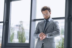 Handsome businessman in eyeglasses looking at watch to check time Stock Photos