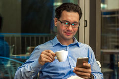 Handsome businessman in eyeglasses is using a smartphone, holding a cup of coffee and smiling while standing near the window. Royalty Free Stock Photo