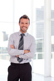 Handsome businessman with folded arms Stock Photography