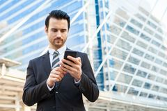 Handsome businessman in formal suit looking at smart phone scree. N Stock Image