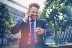 Handsome businessman gesturing while talking on mobile phone Stock Image