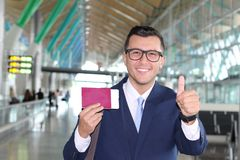 Handsome businessman giving thumbs up at the airport Royalty Free Stock Images