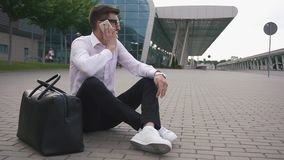 Handsome businessman in glasses at the airport sitting on the ground with luggage and talks by phone trying to solve the. Problem with his retarded flight stock footage