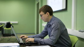 Handsome businessman in glasses sitting at the desk, typing on his laptop and speaking with the audience. Man working on the computer in a coworking center stock video footage