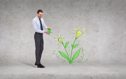Handsome businessman with green watering can Royalty Free Stock Photos