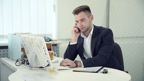 Handsome businessman has bad news by phone. Handsome businessman typing information on a desktop computer in a modern white office concentrating on his work, and stock footage