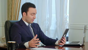 Handsome businessman has meeting on tablet with documents on the desk in office stock footage