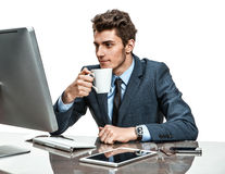 Handsome businessman having a coffee-break in office sitting at the table Royalty Free Stock Image