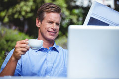 Handsome businessman having coffee and reading the news Stock Photos