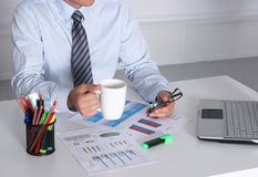 Handsome businessman having tea or coffee in office Stock Photography