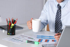 Handsome businessman having tea or coffee in office Stock Photo