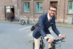 Handsome businessman heading to work by bike.  Royalty Free Stock Image