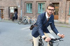 Handsome businessman heading to work by bike.  Royalty Free Stock Photo
