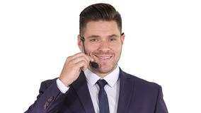 Handsome businessman with headset looking into camera and smiling on white background. stock video