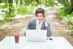Handsome Businessman with headset sitting at the office desk with laptop computer and cup of coffee in call center in green forest Stock Photos