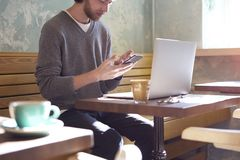 Handsome businessman hipster with long hair working on laptop in sunny cafe, calling someone bt smartphone, having coffee.=. Handsome businessman hipster with royalty free stock image