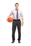 Handsome businessman holding a basketball Royalty Free Stock Photography