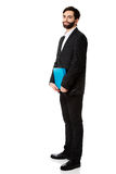 Handsome businessman holding a binder. Happy handsome businessman holding a binder Stock Photography