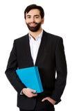Handsome businessman holding a binder. Royalty Free Stock Image