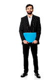 Handsome businessman holding a binder. Happy handsome businessman holding a binder Royalty Free Stock Images