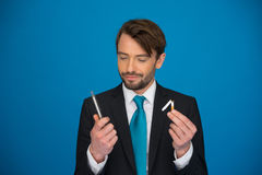 Handsome businessman holding broken cigarette and e-cigarette in the other hand Stock Photos