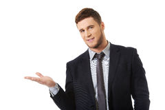 Handsome businessman holding copyspace on palm. stock photo