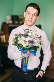Handsome businessman holding flowers and looking at camera indoors Royalty Free Stock Photo