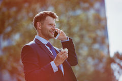 Handsome businessman holding food while talking on mobile phone Royalty Free Stock Images