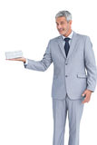 Handsome businessman holding gift and looking at camera Royalty Free Stock Photo