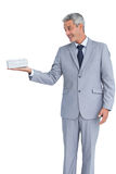 Handsome businessman holding gift on right hand Stock Photos