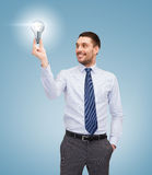 Handsome businessman holding light bulb Stock Images