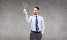 Handsome businessman holding light bulb Stock Photos