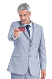Handsome businessman holding and looking at credit card Royalty Free Stock Photos
