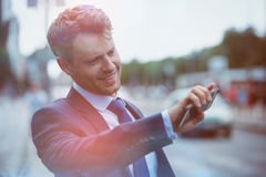 Handsome businessman holding mobile phone and hailing taxi Royalty Free Stock Images