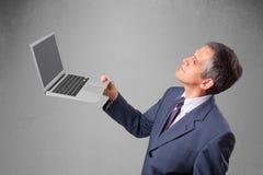 Handsome businessman holding modern laptop Stock Photo
