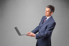 Handsome businessman holding modern laptop Stock Images