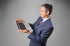 Handsome businessman holding modern laptop Royalty Free Stock Images