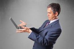 Handsome businessman holding modern laptop Royalty Free Stock Images