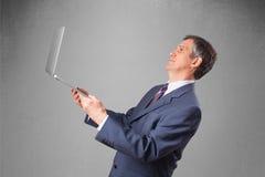 Handsome businessman holding modern laptop Stock Images