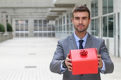 Handsome businessman holding a present stock images