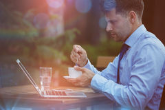 Handsome businessman holding tea while using laptop Royalty Free Stock Photos