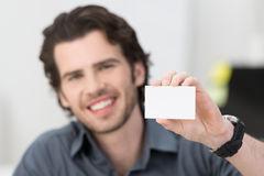 Handsome businessman holding up his card Stock Photos