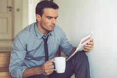 Handsome businessman at home. Handsome businessman in classic suit is holding a cup and reading a newspaper while sitting on the stairs at home Royalty Free Stock Images