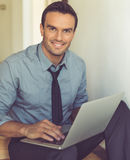 Handsome businessman at home. Handsome businessman in classic suit is using a laptop, looking at camera and smiling while sitting on the stairs at home Royalty Free Stock Photos